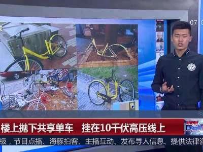[视频]悬!楼上抛下共享单车 挂在10千伏高压线上